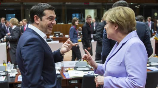 Greek Prime Minister Alexis Tsipras talks with German Chancellor Angela Merkel at a European Union leaders summit in Brussels.