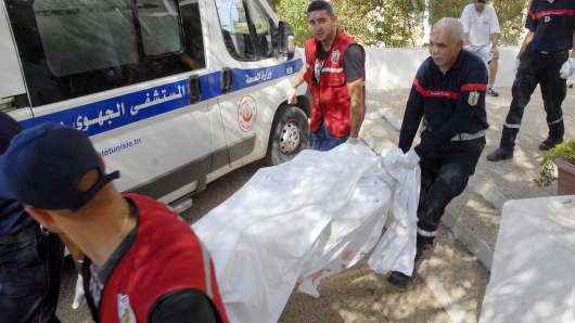 Rescuers carry the body of a tourist who was shot dead by a gunman at a beachside hotel in Sousse, Tunisia, June 26, 2015.