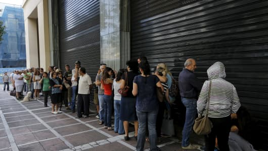 People wait outside a closed branch of Piraeus Bank in Athens, Greece June 27, 2015. The specific branch opens at 10:30 AM local time on Saturdays but it remained closed while dozens of people lined outside to withdrew cash.