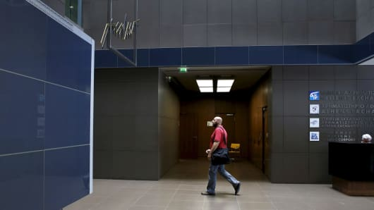 A man walks under switched off share price tickers and screens as the Athens' Stock Exchange is shut after the Greek government imposed capital controls June 29, 2015.