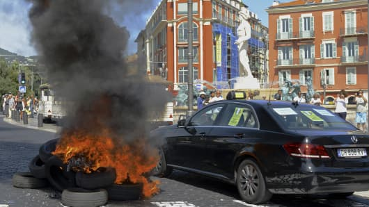 A taxi drives past burning tires during a national protest against car-sharing service Uber in Nice, France, June 25, 2015.