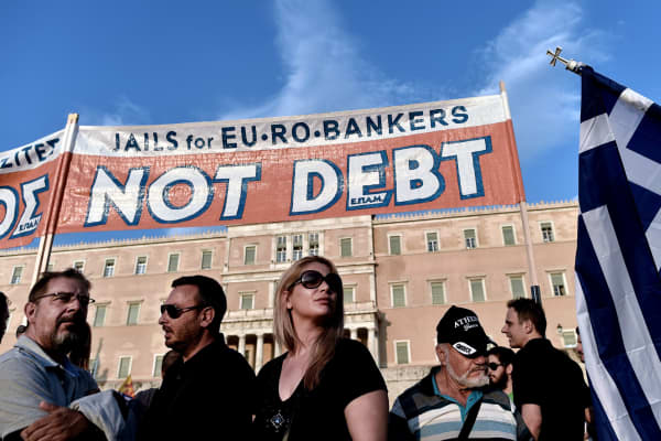 Prostestors stand below a banner reading ''No Debt'' in reference to the forthcoming referendum on bailout conditions set by the country's creditors, during a demonstration in front of the Greek parliament in Athens on June 29, 2015.