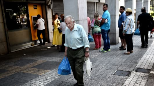 An elderly man walks in front of a bank as people queue to withdraw cash from an ATM machine in central Athens on June 30, 2015.