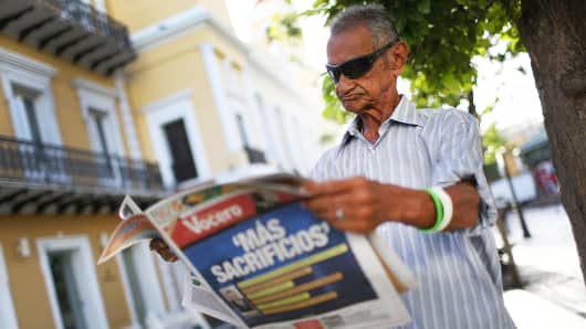 A man reads a newspaper with a Spanish headline that reads, 'More sacrifices,' a day after the speech by Puerto Rican Gov. Alejandro Garcia Padilla regarding the government's debt on June 30, 2015, in San Juan.