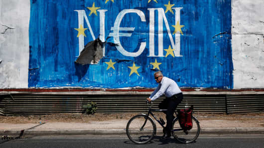 A cyclists passes graffiti street art on a billboard showing the stars of the European Union flag and the German word 'Nein', in Athens, Greece, on Tuesday, June 30, 2015.