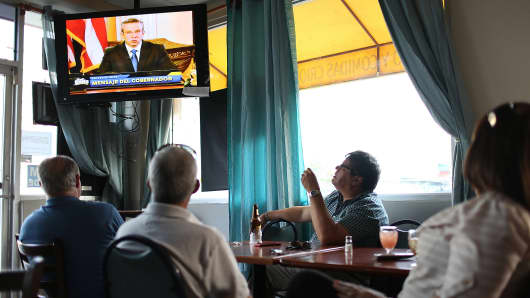 People listen as Puerto Rico Gov. Alejandro Garcia Padilla addresses the island's residents in a televised broadcast regarding the governments $73 billion debt, in San Juan, Puerto Rico, June 29, 2015.