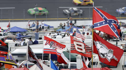 A Confederate flag flies in the infield as cars come out of turn one during a NASCAR auto race at Talladega Superspeedway in Talladega, Ala., Oct. 7, 2007.