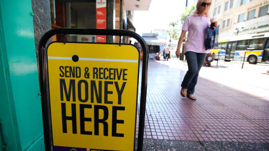 A pedestrian passes an advertising board outside a Western Union money transfer store in Athens, Greece.