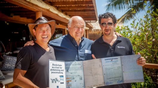 """The Mystery of Capital"" author Hernando DeSoto (center) displaying layers of land titles that can be consolidated into a few lines of code on the block chain.  With Bill Tai (left) and George Kikvadze, vice chairman of BitFury (right)."