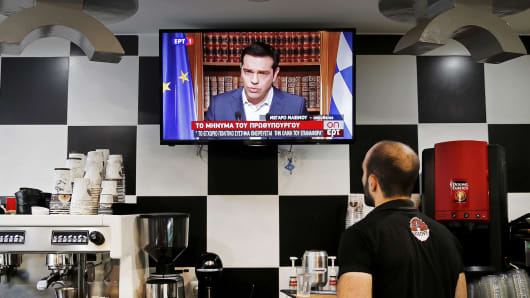 A waiter at a coffee shop follows Greek Prime Minister Alexis Tsipras live television address in Athens, Greece, July 1, 2015.