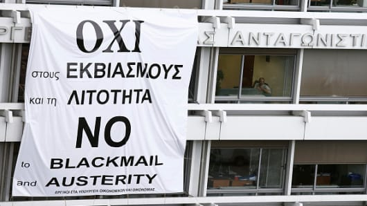 A banner which reads 'No To Blackmail And Austerity' hangs across windows outside the Ministry of Finance after being placed there by employees in Athens, Greece, on Wednesday, July 1, 2015.