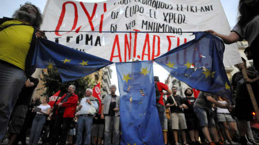 Anti-EU protesters hold a burned and torn European Union flag during a protest at the northern city of Thessaloniki, Greece July 1, 2015. A defiant Prime Minister Alexis Tsipras urged Greeks on Wednesday to reject an international bailout deal, wrecking any prospect of repairing broken relations with EU partners before a referendum on Sunday that may decide Greece's future in Europe.