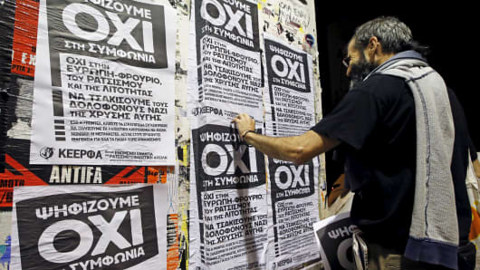 "A man puts up referendum campaign posters with the word ""No"" in Greek in Athens, Greece, July 1, 2015."