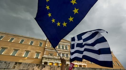 Protesters wave Greek and EU flags during a pro-euro rally in front of the Parliament building, in Athens, on June 30, 2015.