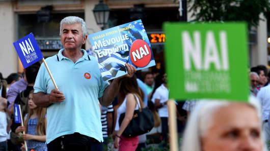 Pro-European Union protesters hold flags and placards reading ''yes'' during a demonstration in Thessaloniki, Greece, on July 2, 2015.