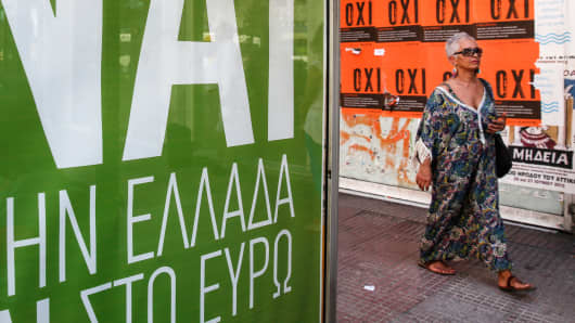 A pedestrian walks between yes, left, and no posters ahead of Sunday's referendum in Athens, Greece, on Thursday, July 2, 2015.