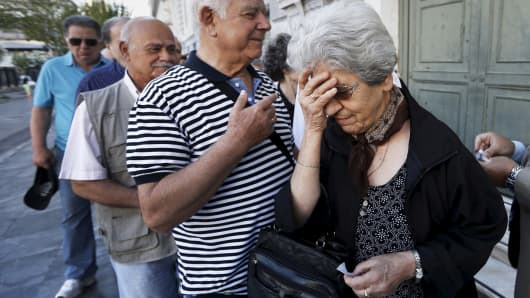 A pensioner reacts after receiving a priority ticket to receive part of their pensions outside a bank in Athens, Greece, July 2, 2015.