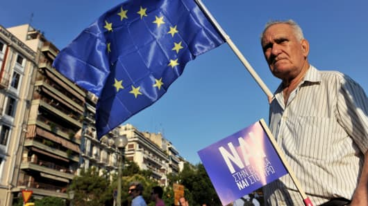 A pro-European Union protester holds an EU flag and a placard reading ''yes'' during a demonstration in Thessaloniki, Greece on July 2, 2015.