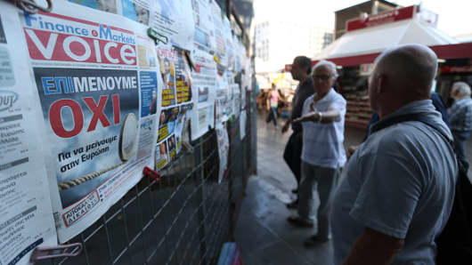 People read newspaper front pages as they hang outside a news kiosk in the Plaka district of Athens, Greece, on Thursday, July 2, 2015.