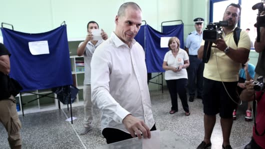 Greek Finance Minister Yanis Varoufakis (C) votes during the Greek referendum in Athens on July 5, 2015.