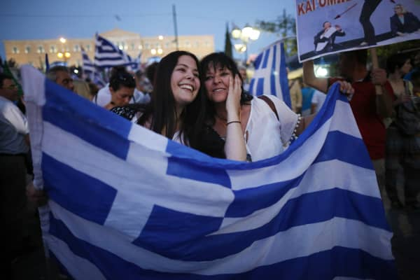 People celebrate in front of the Greek parliament as early opinion polls predict a win for the Oxi, or No, campaign in the Greek austerity referendum. Crowds are begining to gather in the squares of Athens waiting for the official result on July 5, 2015 in Athens, Greece.