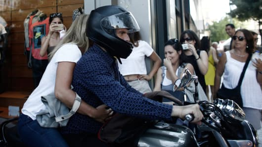 Yanis Varoufakis, Greece's outgoing finance minister, leaves the finance ministry on his motorcycle with Danai Varoufakis, his wife, following his resignation in Athens.