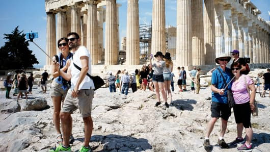 Tourists visit the ancient Acropolis hill, with the ruins of the fifth century BC Parthenon temple on June 30, 2015 in Athens, Greece.