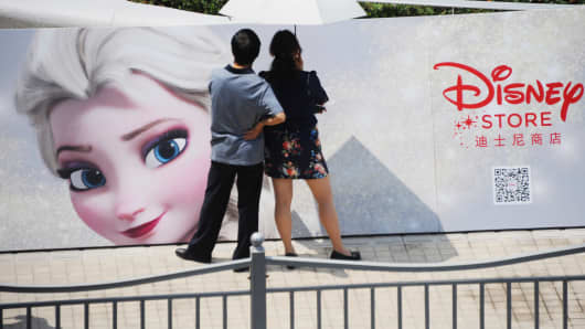 A man and a woman look watch the opening ceremony of the world's largest Disney flagship store in Shanghai, last May.