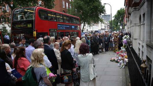 Buses pass by as family members attend a remembrance ceremony at the spot where 13 people were killed in the London bombings on July 7.