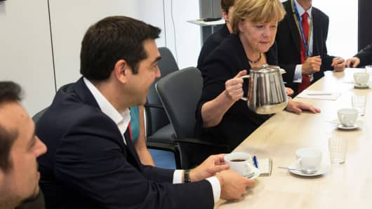 Greek Prime Minister Alexis Tsipras (L) and German Chancellor Angela Merkel (R) attend a meeting with European Commission President Jean-Claude Juncker and French President Francois Hollande (not seen) prior to a euro zone leaders summit in Brussels, Belgium, July 7, 2015.