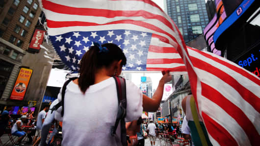A woman walks with an American flag in Times Square, New York.