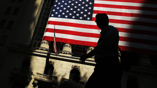 A pedestrian passes in front of the New York Stock Exchange.