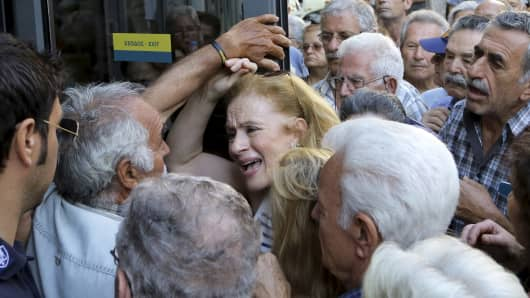 A pensioner tries to enter a National Bank branch to receive part of her pension in the island of Crete, Greece July 9, 2015.