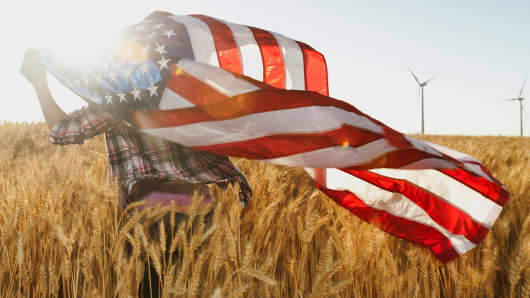 Girl flying American flag in wheat field
