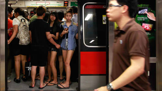 Commuters stand inside a train at the Tanjong Pagar MRT station during rush hour in Singapore.