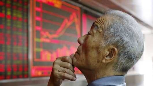 An investor watches an electronic board showing stock information in Beijing.