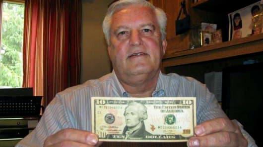 Doug Hamilton holds a $10 bill bearing the portrait of his direct ancestor, Alexander Hamilton, in Columbus, Ohio.