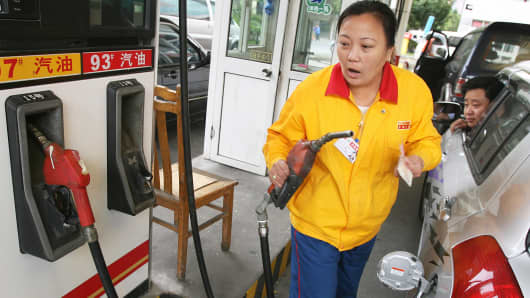 A gas station attendant at pumps gasoline at a PetroChina outlet in Shanghai.