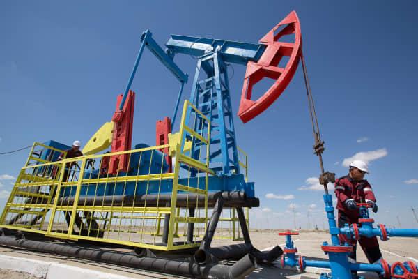 Workers perform maintenance on an oil pumping unit near Atyrau in Kazakhstan.