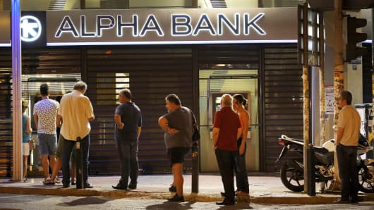 Greeks wait to withdraw money from an ATM in Athens, July 11, 2015.
