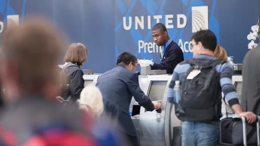 Passengers check-in for flights with United Airlines at O'Hare Airport.