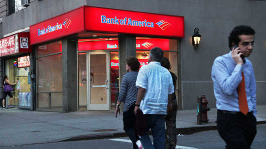 Pedestrians pass in front of a Bank of America branch in New York.