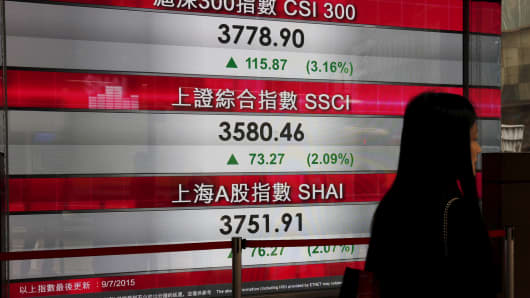 A panel outside a bank displays the morning trading of CSI300 index, the largest listed companies in Shanghai and Shenzhen, and the Shanghai Composite Index, in Hong Kong, China, on July 9, 2015.