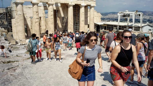 Tourists visit the ancient Acropolis hill, with the ruins of the Parthenon temple in Athens.