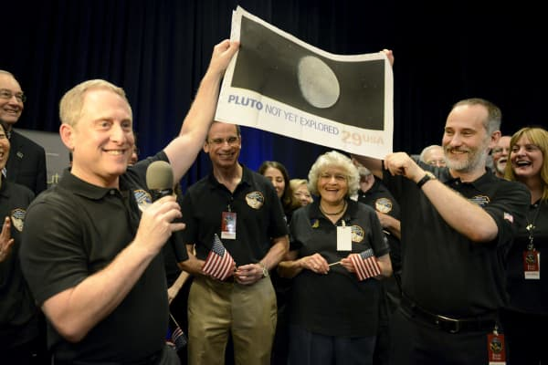 "NASA Principal Investigator for New Horizons mission Alan Stern (L) and Co-Investigator Will Grundy (R) hold up an enlarged, out-dated U.S. postage stamp with the words ""PLUTO NOT YET EXPLORED"", during the celebration of the spacecraft New Horizons flyby of Pluto, at NASA's Johns Hopkins Applied Physics Laboratory in Laurel, Maryland, July 14, 2015."