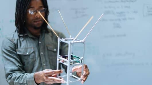Spire Engineer Holds a 2U Cubesat Model