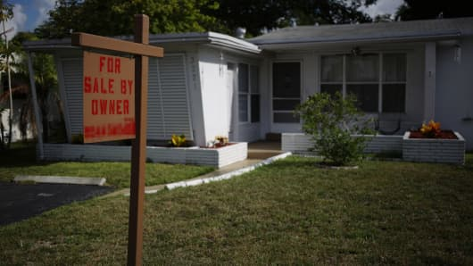 A 'For Sale By Owner' sign stands in front of a house in Fort Lauderdale, Florida.