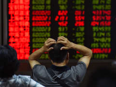 An investor looks at screens showing stock market movements at a securities company in Beijing