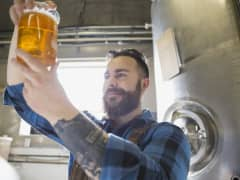 Brewery worker examining beer in beaker. Craft breweries continue to grow.