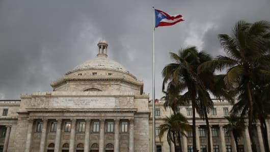 The Puerto Rican flag flies near the Capitol building as the island's residents deal with the government's $72 billion debt on in San Juan, Puerto Rico